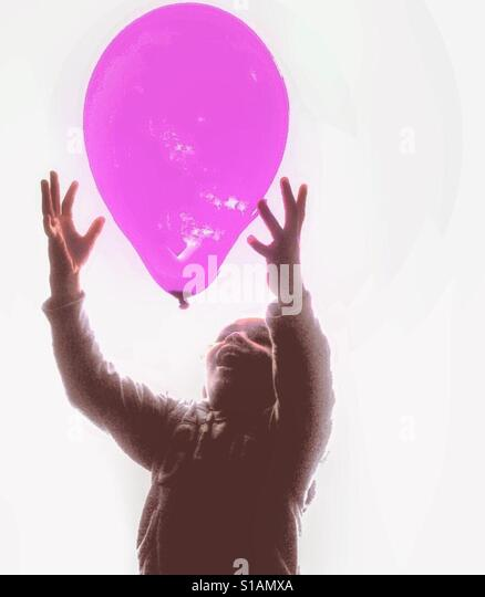 A child plays with a ballon - Stock Image