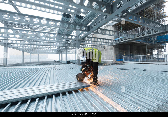 Workman cutting steel flooring on a building site in full protective clothing - Stock Image
