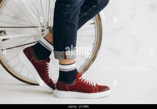 Legs of man standing near bicycle wheel - Stock Image