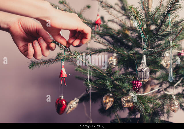 Hands decorating a christmas tree with all kinds of colorful things - Stock Image