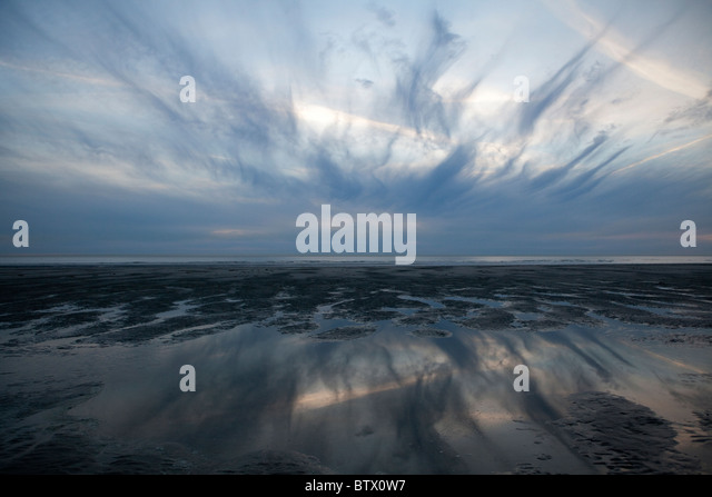 Dramatic sky reflecting in water at sunset on beach, at Le Touquet, France - Stock Image