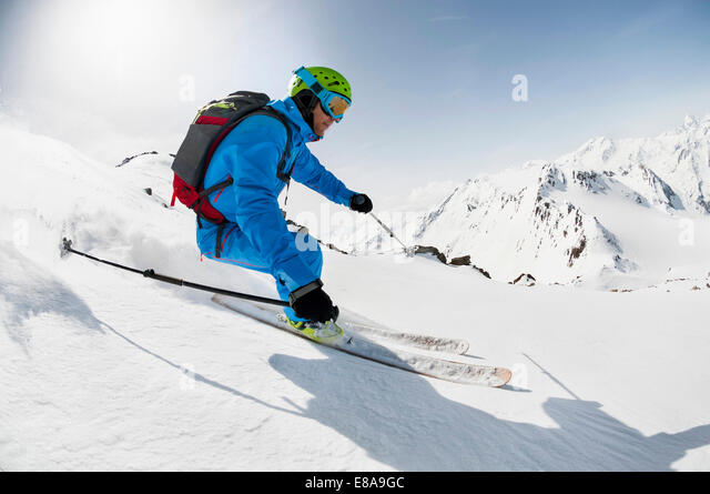 Man skier skiing downhill steep slope Alps - Stock-Bilder