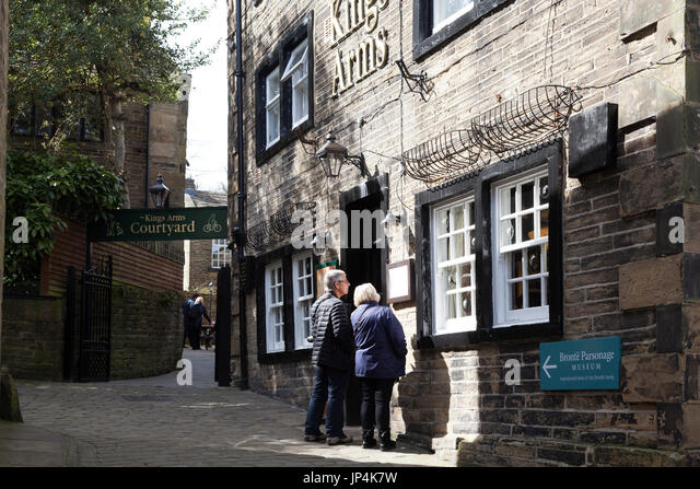 Visitors exploring the cobbled streets of Haworth, West Yorkshire - Stock Image