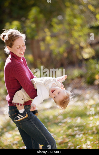Mother playfully swings son - Stock Image