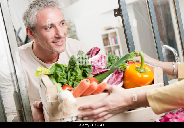 Passing a crate of organic vegetables - Stock Image