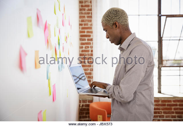 Young man standing in front of white board with sticky notes, using laptop - Stock-Bilder