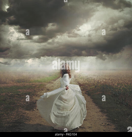 Woman dancing in desolate road. Dramatic and surreal cloudscape - Stock-Bilder