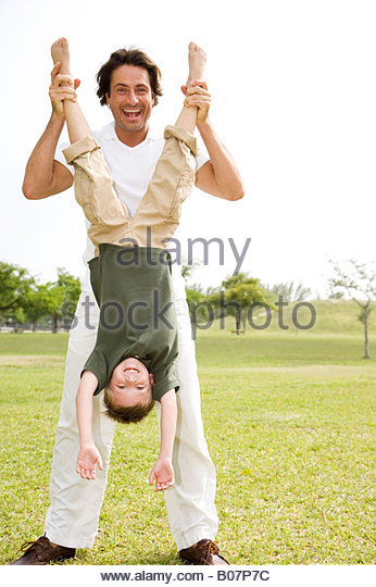father holding son upside down in the park - Stock Image