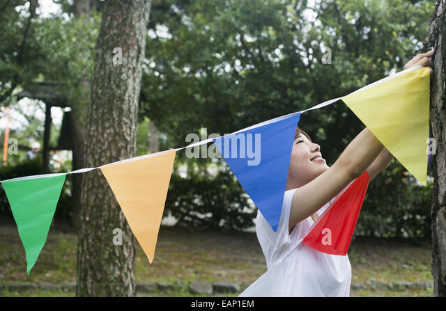 A woman in a Kyoto park holding up a colourful row of flags. - Stock Image
