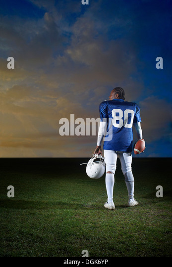 Rear view of American football player holding helmet - Stock-Bilder