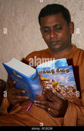 Hindu Man reading The Bhagavad Gita , A Hindu Holy book , in the Indian language Tamil India - Stock Image