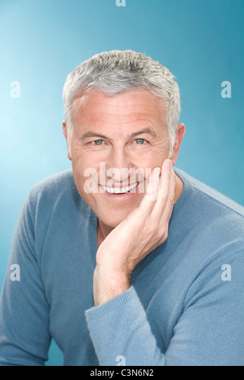 Happy grey hair man with hand to face - Stock Image