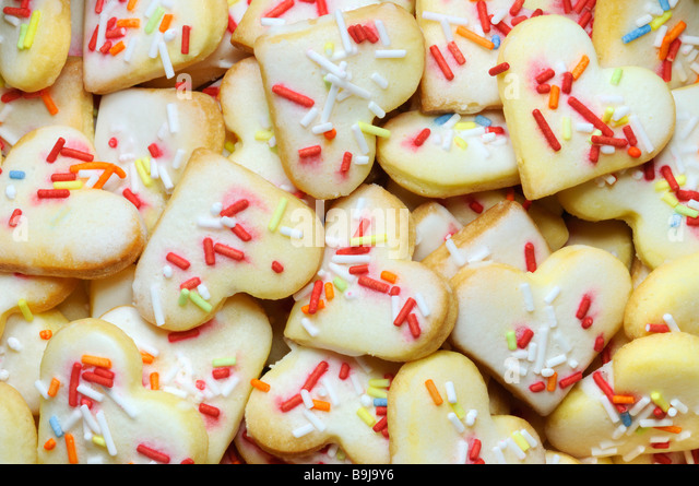Heart-shaped short pastry biscuits with multicoloured sugar sprinkles, filling the picture - Stock Image