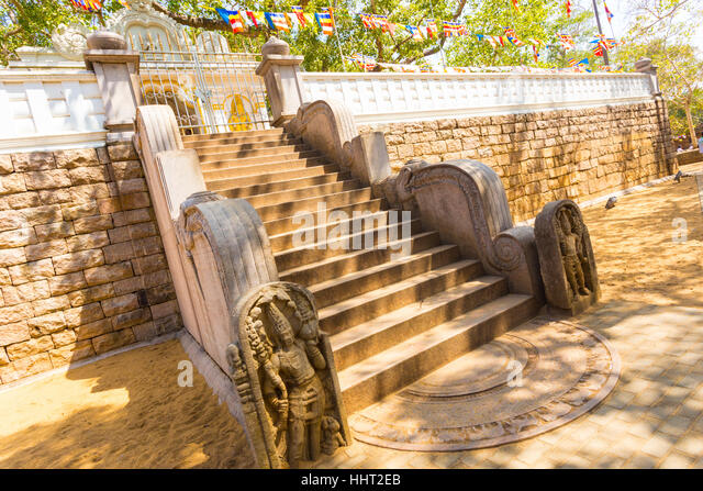Carved moonstone at the base of the compound steps to enter Jaya Sri Maha Bodhi containing the sacred fig tree in - Stock Image