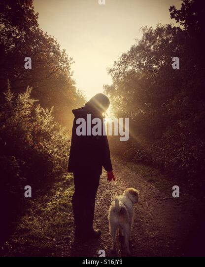 Woman and her dog on a path at sunrise - Stock-Bilder