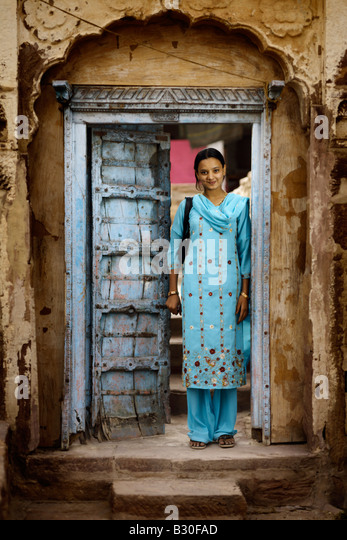 A young Indian woman dressed in blue stands in a blue doorway of her aged rural home. - Stock-Bilder