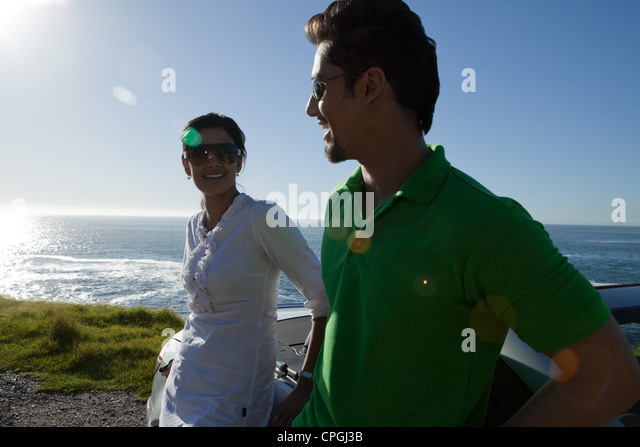 Couple leaning against convertible by the sea. - Stock-Bilder