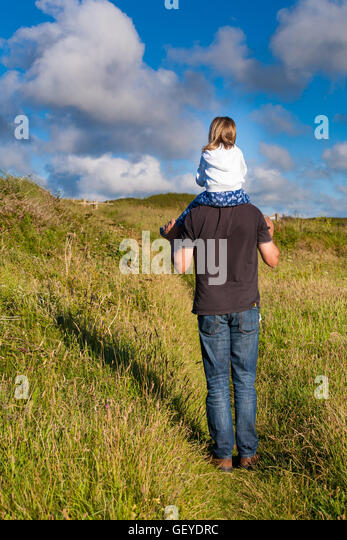 Father and daughter. Daddy carrying little girl. Dad giving female kid a shoulder ride. Parenting family concept. - Stock Image