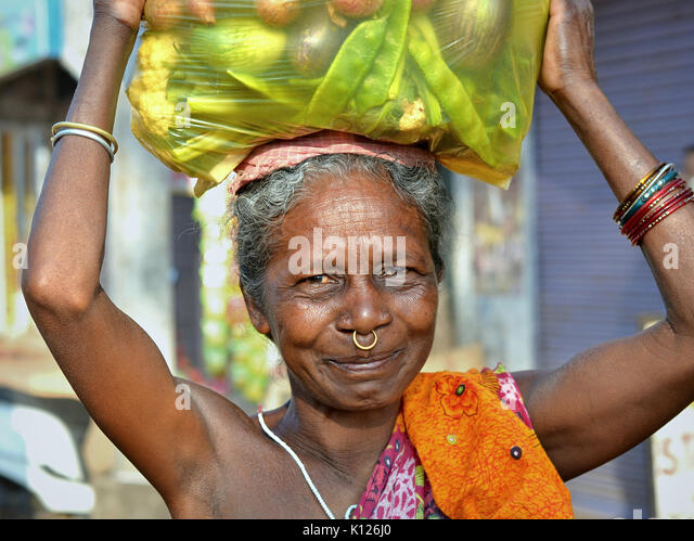 Elderly Indian Adivasi woman (Orissan tribal woman) with one golden nose ring, carrying on her head a heavy plastic - Stock Image