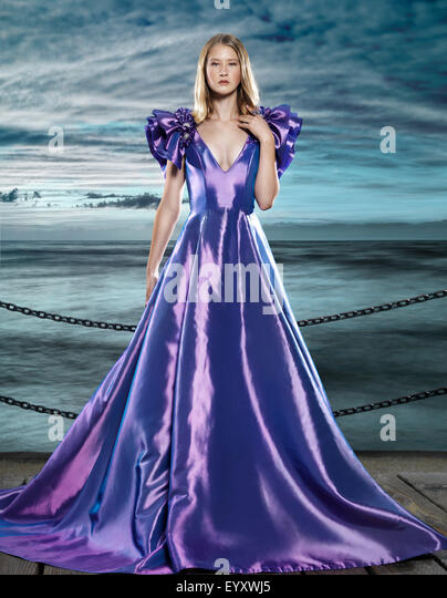Young blond woman wearing a beautiful long blue dress, evening gown, at waterfront, artistic fashion portrait - Stock Image
