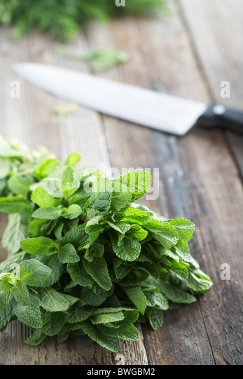 Fresh mint on rough table with knife - Stock Image