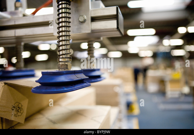Pneumatic handling robot with technical springs and suction cups designed to lift cardboard boxes in warehouse - Stock Image