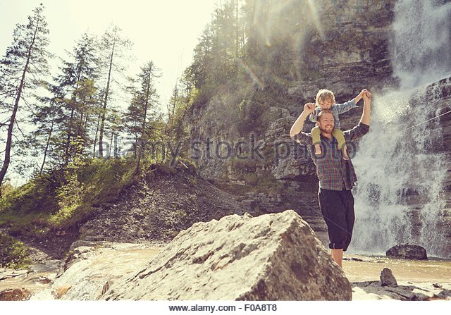 Two generation family having fun by waterfall, Ehrwald, Tyrol, Austria - Stock Image