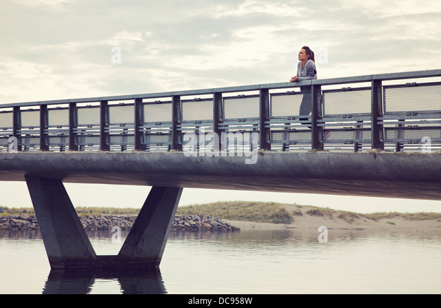 Woman alone on the bridge against cloudy sky - Stock Image