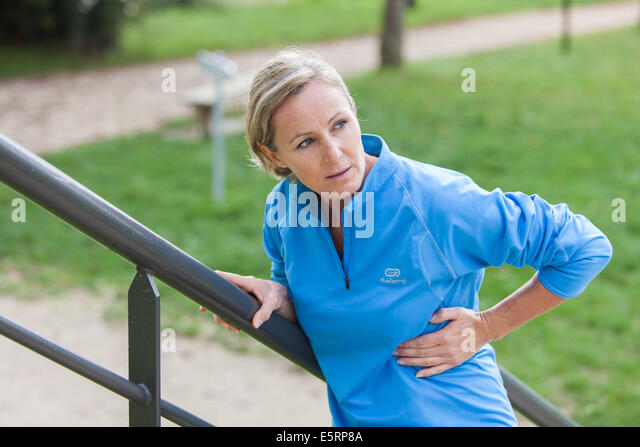 Woman suffering from a stitch. - Stock Image