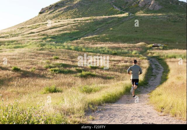 Rear view of young male runner running up hillside track - Stock Image