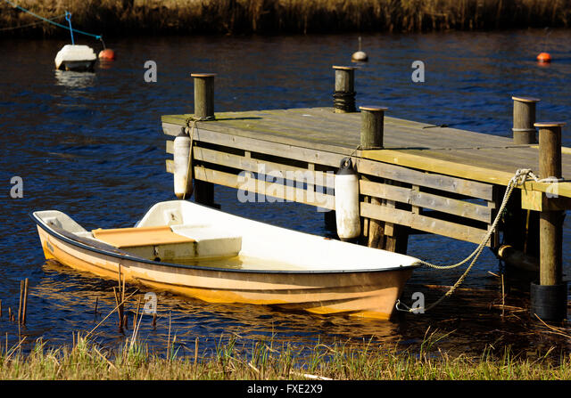 Orange plastic rowboat filled with water moored at a wooden pier in spring. - Stock Image
