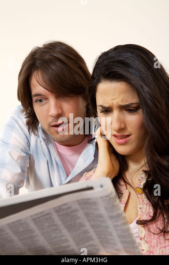 Couple searching for a home in the newspaper - Stock Image