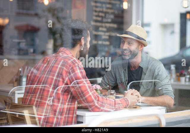Gay couple sat holding hands in cafe - Stock-Bilder