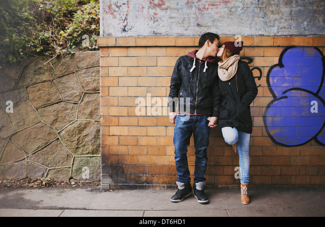 Affectionate teenage couple kissing outdoors against a wall on street. Mixed race couple in love. - Stock-Bilder
