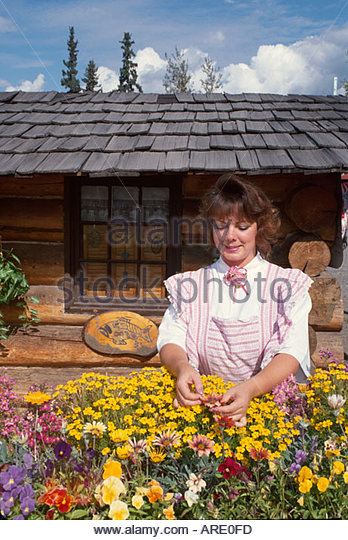 Alaska Fairbanks Alaskaland Pioneer Theme Park trapper's cabin pioneer woman flower garden - Stock Image