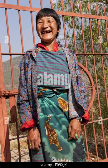 Woman smiling widely and standing against iron gate in Paro, Bhutan - Stock Image