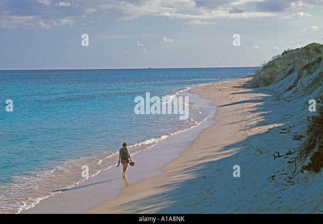 Anguilla beach single woman walking alone deserted beach - Stock Image