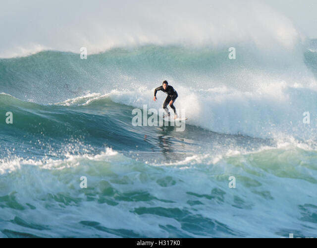 surfers ride huge waves weather generated by Hurricane Matthew at Fistral Bay UK 3rd October 2016. - Stock Image