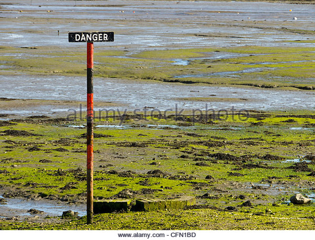 Danger Warning Sign soft Mud on Shore Tide out Langstone Hampshire England UK - Stock Image