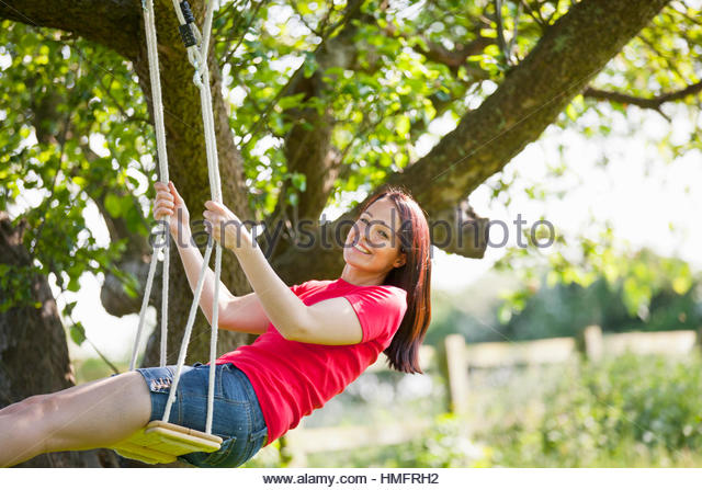 Portrait happy woman swinging on tree swing in sunny summer rural yard - Stock-Bilder