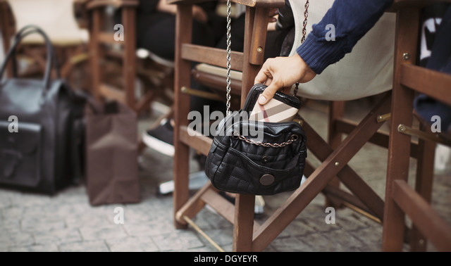 Man taking wallet out of a woman's purse at street cafe during daytime. Thief stealing purse. Pickpocketing - Stock Image