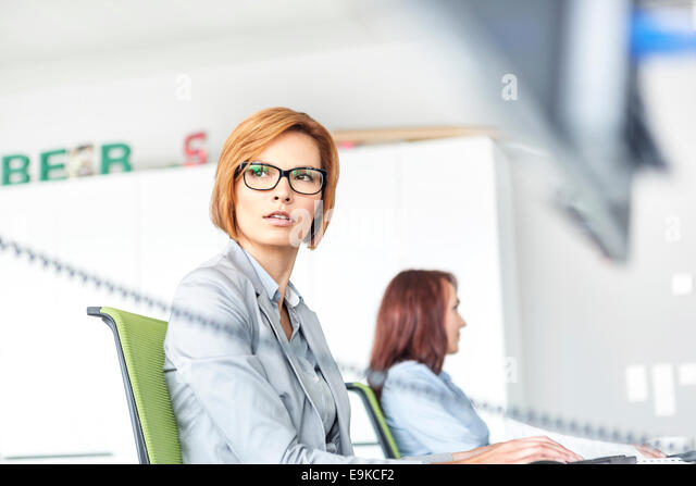 Young businesswoman working on computer with colleague in background at office - Stock Image