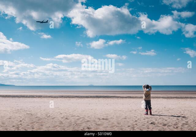 Young boy standing on a beach watching a plane fly by - Stock Image