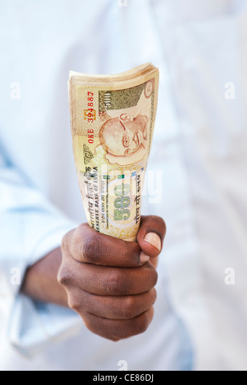 Indian mans hand holding a bunch of 500 rupee notes - Stock-Bilder