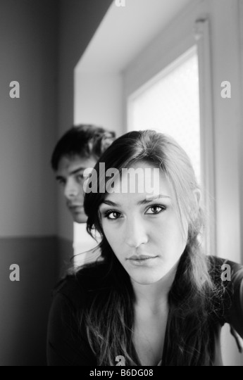 Pensive woman by the window- young couple - Stock Image