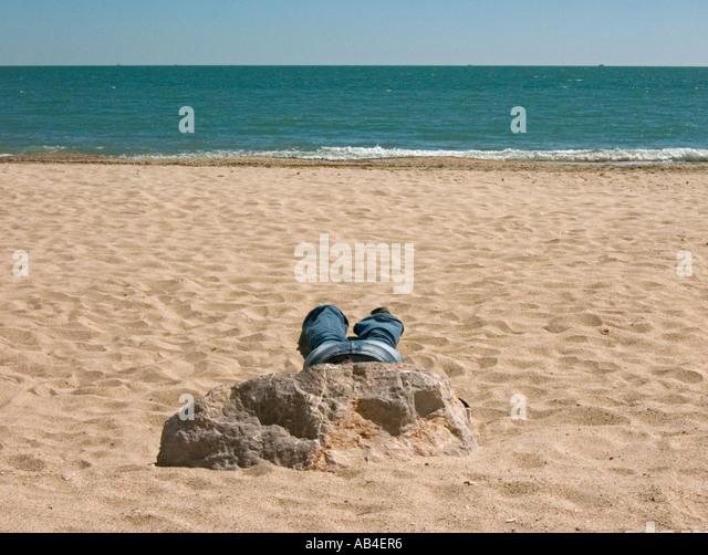 lone sunbather in jeans asleep behind rock on palavas beach - Stock Image