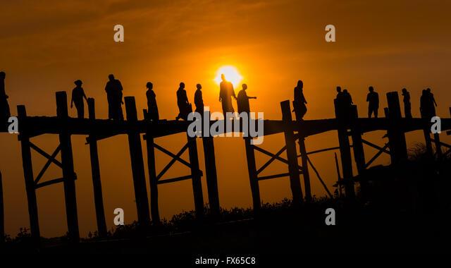 A group of people crossing the wooden U-Bein Bridge, Amarapura township, at sunset. - Stock-Bilder
