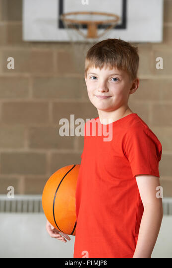 Portrait Of Boy Holding Basketball In School Gym - Stock Image