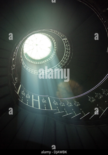 Delicate sunlights among wooden spiral stairs - Stock Image