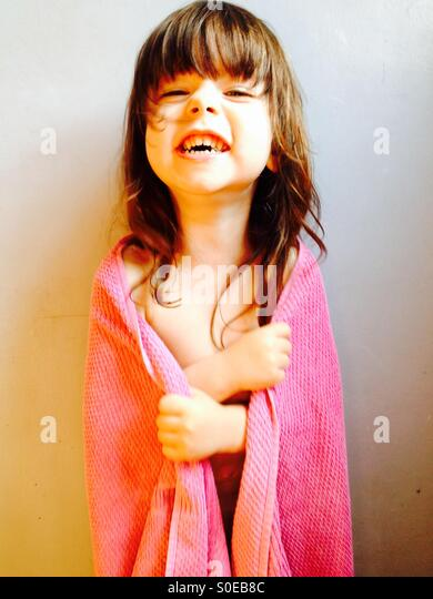 3-year old girl laughing while wrapped up in a pink towel after a bath - Stock Image